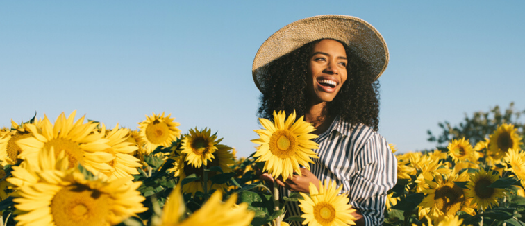 Women in field of sunflowers smiling