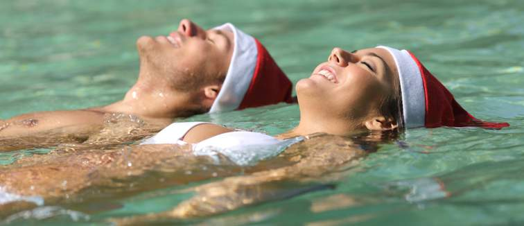 Man and woman floating in a pool wearing Santa hats