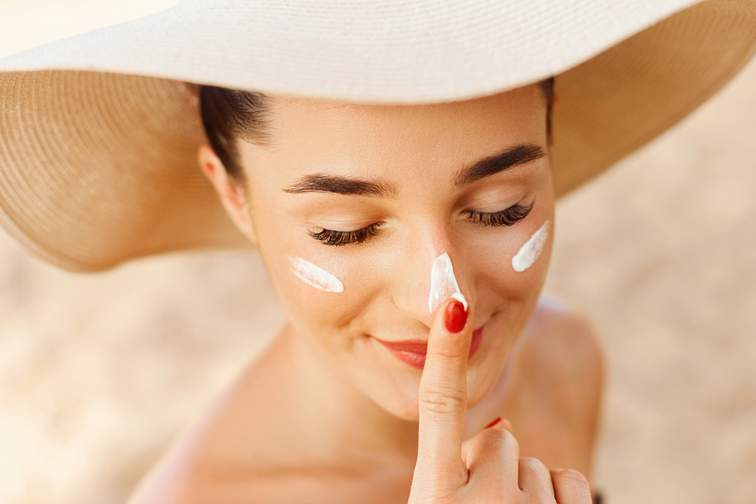 Woman dotting sun tan lotion onto face