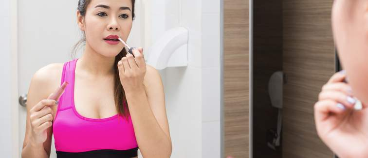 woman applying makeup in the gym