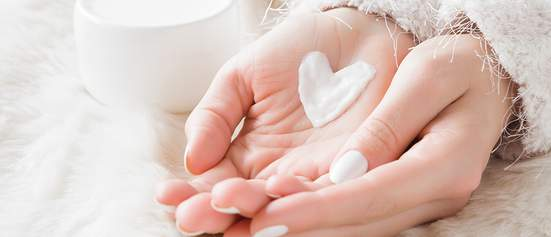Cupped hands holding cream in heart shape